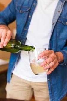 Primer plano de un hombre que vierte cerveza en vidrio
