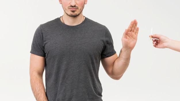 El primer plano de un hombre rechaza el cigarrillo ofrecido por una persona aislada en el fondo blanco