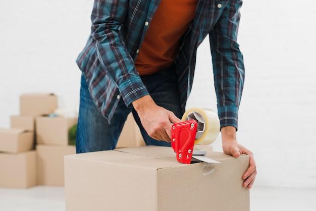 Primer plano de un hombre sellando caja de cartón con cinta adhesiva