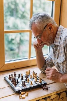 Primer plano de hombre senior jugando al ajedrez en el alféizar de la ventana
