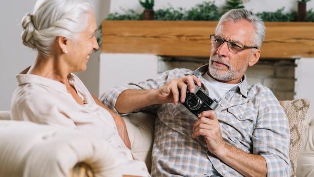 Primer plano de hombre senior sosteniendo la cámara en la mano mirando a su esposa sentada en el sofá