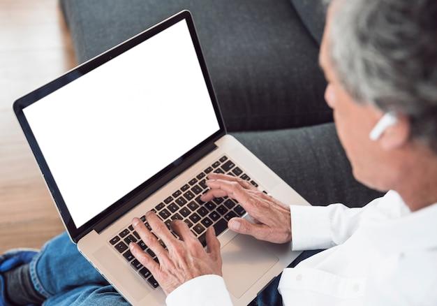 Primer plano de hombre senior usando laptop con pantalla blanca
