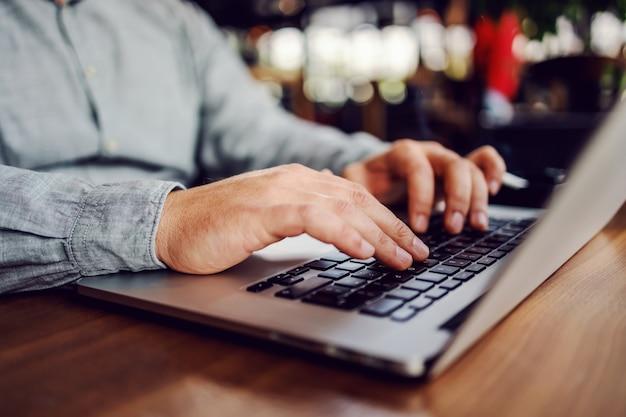 Primer plano de un hombre sentado en el restaurante y escribiendo en la computadora portátil.