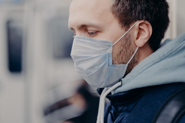 Primer plano de un hombre serio que camina en lugares concurridos, viaja al trabajo bajo tierra, usa una máscara médica para protegerse la cara durante un brote y una infección por coronavirus. concepto de protección de la enfermedad
