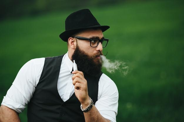Primer plano de hombre con sombrero fumando un cigarro electrónico