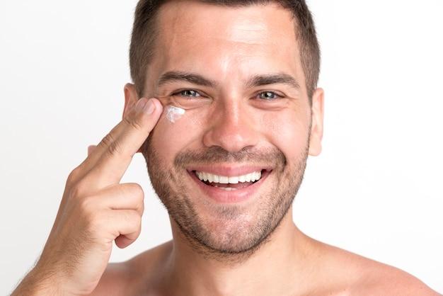 Primer plano de hombre sonriente, aplicar la crema en la cara