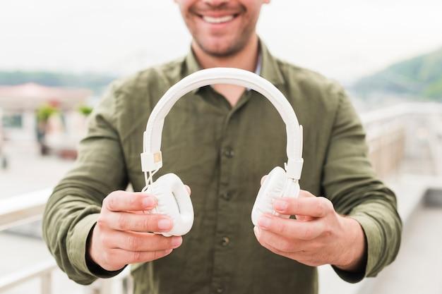 Primer plano de hombre sonriente mostrando auriculares blancos