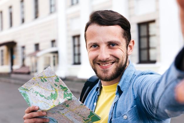 Primer plano de hombre sonriente sosteniendo mapa tomando selfie al aire libre