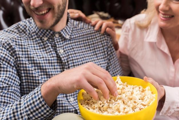Primer plano de hombre sonriente con tazón de palomitas de maíz