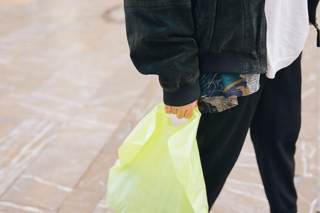 Primer plano de hombre sosteniendo amarillo llevar bolsa de plástico en la mano
