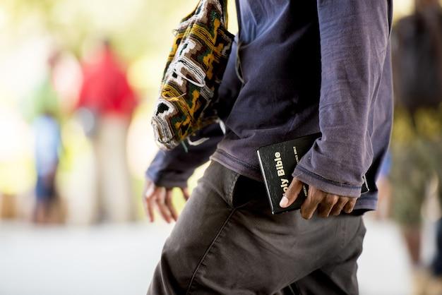 Primer plano de un hombre sosteniendo una biblia caminando en la calle con un borroso