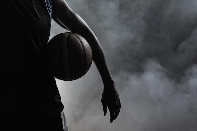Primer plano de un hombre sosteniendo una pelota de baloncesto