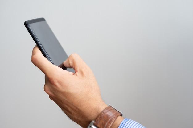 Primer plano de hombre sosteniendo teléfono inteligente y tocando su pantalla