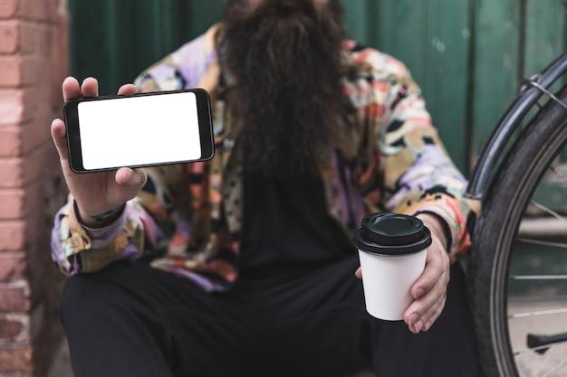 Primer plano de un hombre sosteniendo un teléfono móvil y una taza de café desechable en la mano