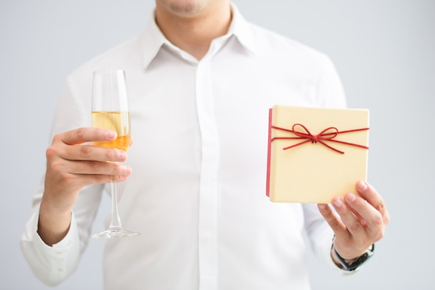 Primer plano de hombre sosteniendo el vaso con champán y caja de regalo