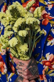 Primer plano de un hombre con un tatuaje en la mano sosteniendo una flor de limonium en la mano