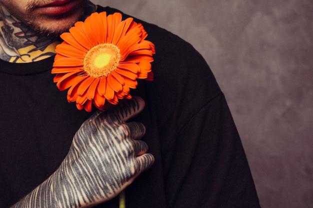 Primer plano de un hombre con tatuaje en su mano sosteniendo una flor de gerbera naranja sobre el hombro