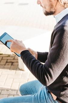 Primer plano de un hombre tocando la pantalla táctil de un teléfono inteligente al aire libre