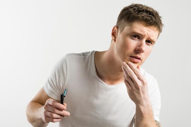 Primer plano de un hombre tocando su piel después de afeitarse sosteniendo la maquinilla de afeitar en la mano contra el fondo blanco