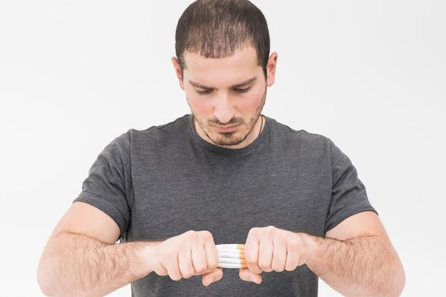 Primer plano de un hombre tratando de romper la pila de cigarrillos con las manos aisladas sobre fondo blanco