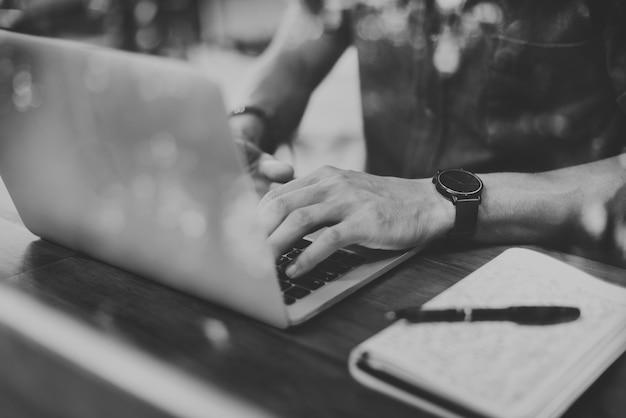 Primer plano de hombre usando laptop en café en escala de grises