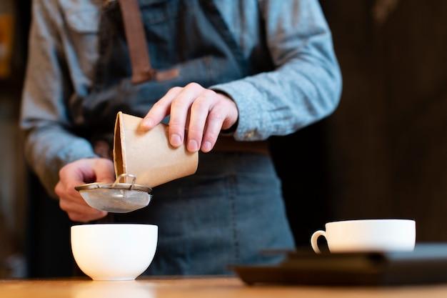 Primer plano del hombre vertiendo café en taza a través del tamiz