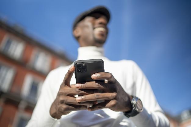 Primer plano de un hombre vestido con un cuello alto y un sombrero sosteniendo su teléfono