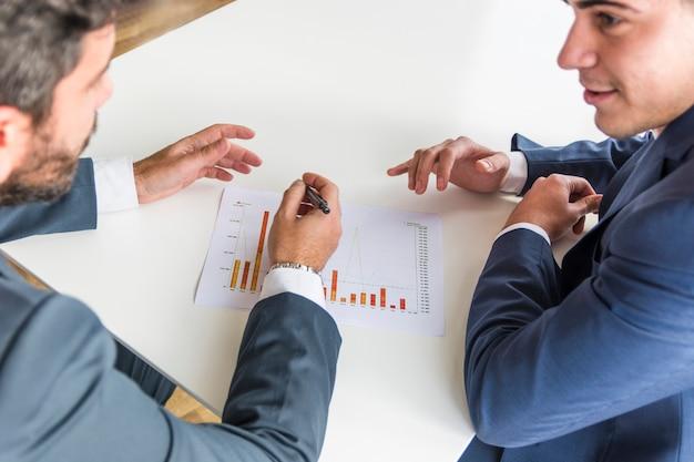 Primer plano de los hombres de negocios que trabajan en el informe financiero de la empresa sobre el escritorio blanco