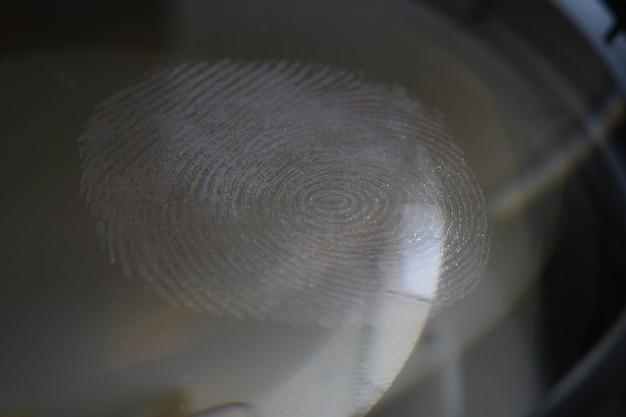 Un primer plano de una huella dactilar sobre el vidrio contra un fondo oscuro tecnología moderna de biometría