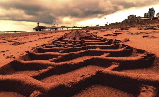 Primer plano de huellas de neumáticos en la arena en el muelle de scheveningen en la haya