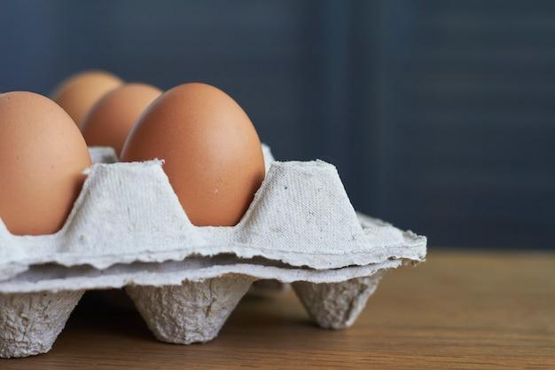 Primer plano de huevos marrones, huevos de gallina en bandeja de cartón sobre mesa de madera