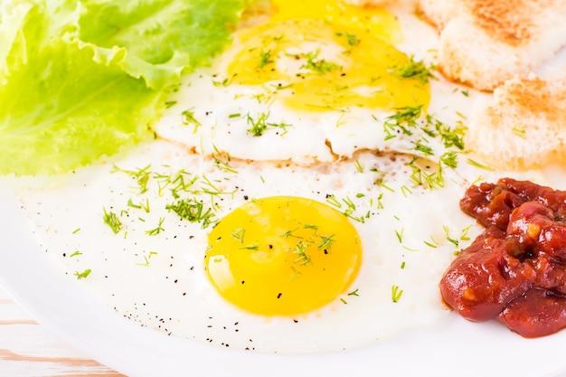 Primer plano de huevos revueltos, pan frito, salsa de tomate y hojas de lechuga en un plato