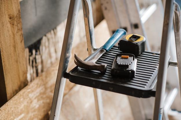 Primer plano de un hummer y herramientas en las escaleras durante la construcción de la casa