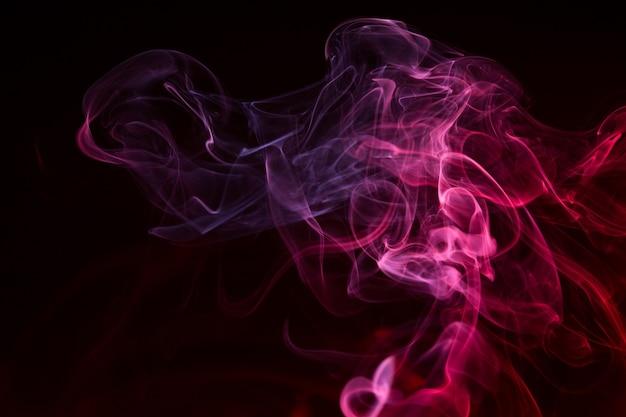 Primer plano de humo de colores sobre un fondo negro