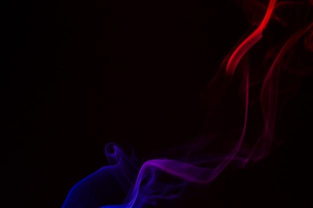 Primer plano de humo colorido sobre un fondo negro