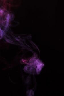 Primer plano de humo púrpura descolorido sobre fondo negro