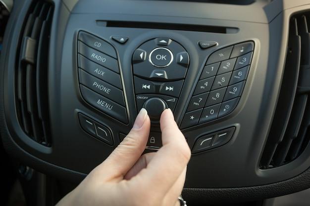 Primer plano de la imagen del conductor femenino ajustando el sistema estéreo del coche