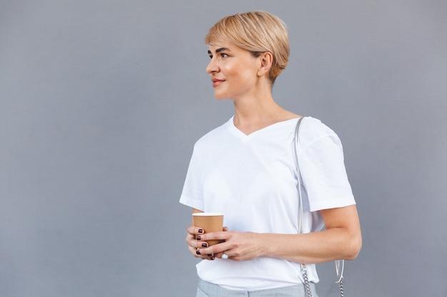 Primer plano de la imagen de una hermosa mujer rubia con camiseta blanca que se encuentran aisladas sobre la pared gris y sosteniendo el café de la taza de papel