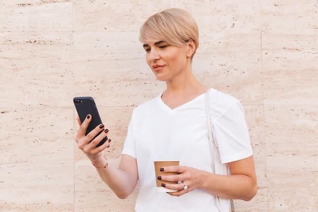 Primer plano de la imagen de una mujer rubia caucásica con camiseta blanca con teléfono celular, mientras está de pie contra la pared beige al aire libre en verano y tomando café de la taza de papel
