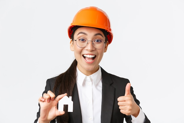 Primer plano de una ingeniera asiática profesional optimista, arquitecta con casco y traje de negocios que anima a ponerse en contacto con su empresa para la renovación y el diseño, mostrando la casa y el pulgar hacia arriba