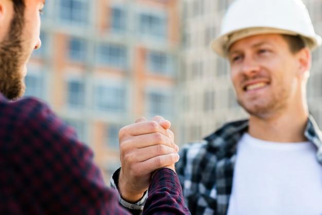 Primer plano de ingeniero y arquitecto dándose la mano