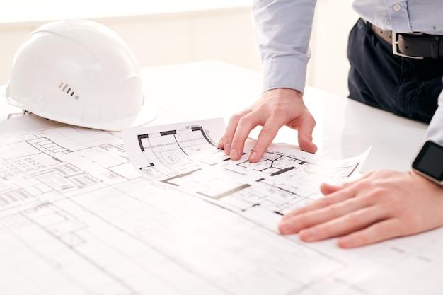 Primer plano del ingeniero irreconocible de pie en la mesa con casco y examinar planos