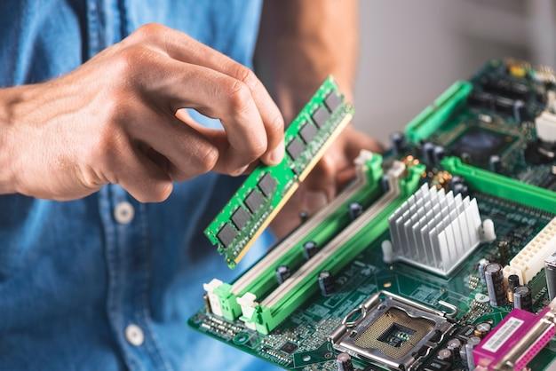 Primer plano de ingeniero poniendo el módulo de memoria ram en la placa base de la computadora