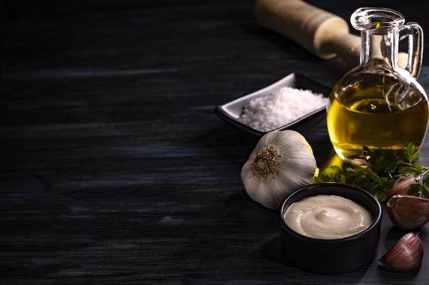 Primer plano de ingredientes como aceite de oliva, sal, ajo, hierbas, salsa