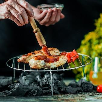 Primer plano de inmersión de salsa de mano en la carne de barbacoa