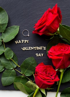 Primer plano de la inscripción del día de san valentín feliz con rosas sobre una superficie negra