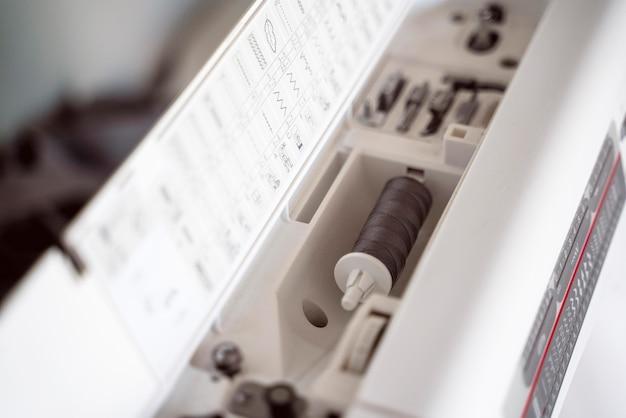 Primer plano interior de la máquina de coser blanca