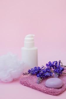 Primer plano de jabón; toalla; flor de lavanda; lufa y botella cosmética en superficie rosa.