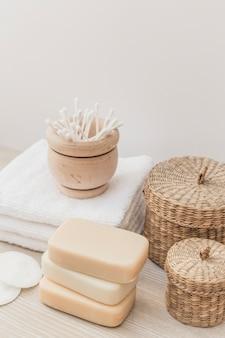 Primer plano de jabones; esponja; bastoncillo de algodón; toalla y cesta de mimbre en superficie de madera.