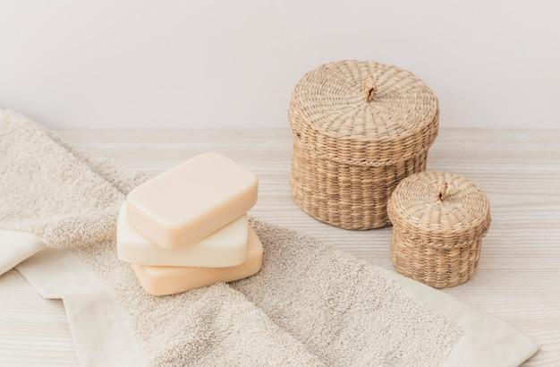 Primer plano de jabones; toalla y cesta de mimbre en superficie de madera.